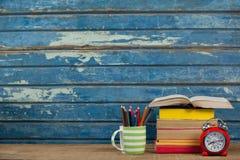 Pila di libri, di sveglia e di supporto della penna Immagine Stock Libera da Diritti