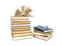 Pila di libri e di vetri su una priorità bassa bianca Fotografie Stock