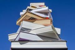 Pila di libri di grandezza di discesa contro un bello cielo blu immagini stock