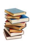 Pila di libri isolati sui precedenti bianchi Fotografia Stock