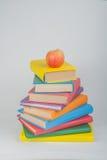Pila di libri reali variopinti, mela su fondo bianco, vista parziale Di nuovo alla scuola, copi lo spazio Istruzione Immagini Stock