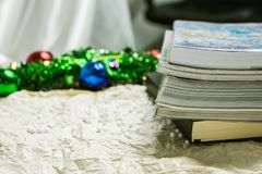 Pila di libri su un crêpe grigio con una campana meravigliosamente colorata immagini stock