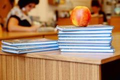 Pila di libri sulla tavola di legno per la lettura con il ap red delicious Immagini Stock Libere da Diritti
