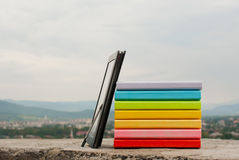 Pila di libri variopinti con il reade del e-libro Fotografie Stock Libere da Diritti