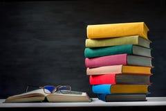 Pila di libri variopinti con quello aperto sulla tavola con glasse immagini stock libere da diritti