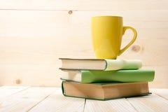 Pila di libri variopinti, di libro aperto e di tazza sulla tavola di legno Di nuovo al banco Copi lo spazio Immagini Stock Libere da Diritti