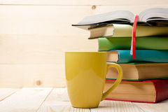 Pila di libri variopinti, di libro aperto e di tazza sulla tavola di legno Di nuovo al banco Copi lo spazio Immagine Stock Libera da Diritti