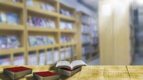 Pila di libro sulla tavola di legno, fondo vago Scaffale per libri in libreria immagine stock