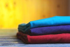 Pila di magliette differenti del cotone sulla tavola di legno Fotografia Stock Libera da Diritti