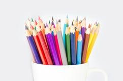 Pila di matite colorate in un vetro su fondo bianco Immagini Stock