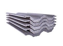 Pila di mattonelle di tetto concrete (colore grigio) su bianco Fotografia Stock