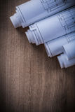 Pila di modelli rotolati sul raggiro di legno della costruzione del fondo Immagini Stock Libere da Diritti