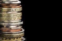 Pila di monete britanniche sopra il nero Fotografie Stock