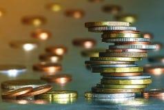 Pila di monete con fondo grigio vago immagini stock