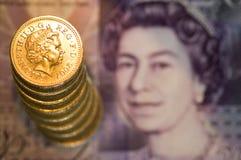 Pila di monete di libbra sulla nota Fotografia Stock Libera da Diritti