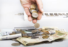 Pila di monete di valuta e note e mano indiane Fotografie Stock Libere da Diritti