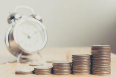 Pila di monete disposte sulle scale sul bordo di legno con l'orologio, Fina Fotografia Stock