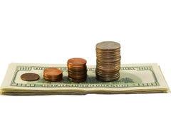 Pila di monete e di dollari fotografia stock
