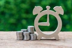 Pila di monete e di sveglia di legno come timeli di scopi di investimento fotografia stock