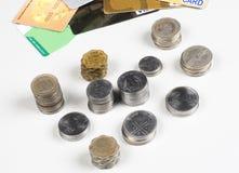 Pila di monete indiane con le carte di credito su bianco Immagini Stock