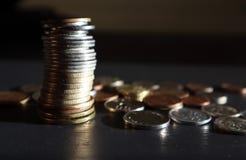 Pila di monete su fondo scuro fotografia stock
