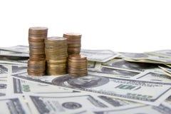 Pila di monete sui dollari Fotografia Stock