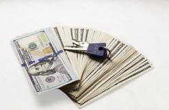 Pila di nuove banconote del cento-dollaro con le chiavi su fondo bianco Soldi di reddito dei guadagni dalle transazioni del bene  Fotografia Stock