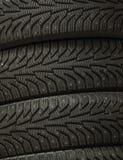 Pila di nuove gomme nere a quattro ruote per il primo piano di macro del fondo di guida di veicoli di inverno Fotografie Stock Libere da Diritti