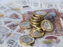Pila di nuove monete di libbra su dieci note della libbra Immagini Stock