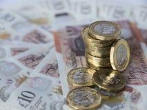 Pila di nuove monete di sterlina su un cerchio dei semi di dieci note della libbra Immagine Stock