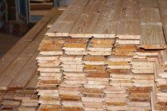 Pila di nuove viti prigioniere di legno all'iarda di legname Immagine Stock