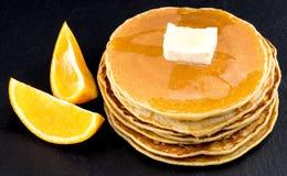Pila di pancake allo sciroppo con le arance su fondo scuro Fotografia Stock Libera da Diritti