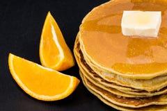 Pila di pancake allo sciroppo con le arance su fondo scuro Fotografie Stock Libere da Diritti