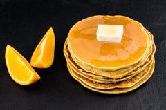 Pila di pancake allo sciroppo con le arance su fondo scuro Immagini Stock