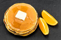 Pila di pancake allo sciroppo con le arance su fondo scuro Fotografia Stock