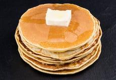 Pila di pancake allo sciroppo su fondo scuro Fotografie Stock Libere da Diritti
