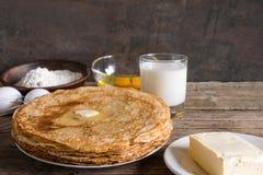 Pila di pancake con burro e gli ingredienti per la prima colazione Fotografia Stock