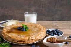 Pila di pancake con i mirtilli, la menta, il miele, il burro ed il latte freschi per la prima colazione Immagine Stock