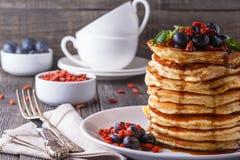 Pila di pancake con il mirtillo, il goji e lo sciroppo d'acero freschi Immagine Stock Libera da Diritti