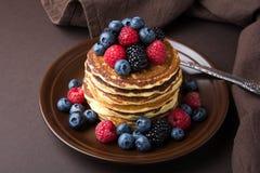 Pila di pancake con il mirtillo, il lampone e la mora freschi sul piatto marrone Fotografie Stock