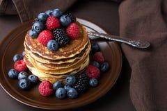 Pila di pancake con il mirtillo, il lampone e la mora freschi sul piatto marrone Fotografie Stock Libere da Diritti