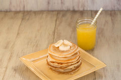 Pila di pancake con le banane ed il succo d'arancia fresco Fotografia Stock