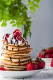 Pila di pancake con le fragole, la crema della frusta e lo sciroppo di cioccolato su un piatto bianco su un fondo bianco Fotografia Stock Libera da Diritti