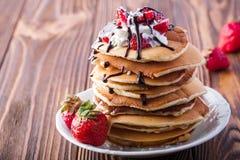 Pila di pancake con le fragole, la crema della frusta e lo sciroppo di cioccolato su un piatto bianco su un fondo di legno Fotografie Stock