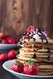 Pila di pancake con le fragole, la crema della frusta e lo sciroppo di cioccolato su un piatto bianco su un fondo di legno Immagine Stock Libera da Diritti