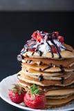 Pila di pancake con le fragole, la crema della frusta e lo sciroppo di cioccolato su un piatto bianco su un fondo nero Fotografie Stock