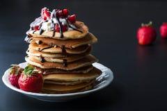 Pila di pancake con le fragole, la crema della frusta e lo sciroppo di cioccolato su un piatto bianco su un fondo nero Immagini Stock Libere da Diritti