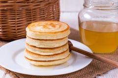 Pila di pancake con miele in piatto sulla tavola bianca immagini stock libere da diritti