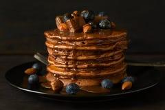 Pila di pancake del cioccolato con glassa, il mirtillo, la mandorla, la nocciola ed i pezzi di cioccolato Immagine Stock