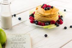 Pila di pancake dolci con il mirtillo, il lampone, Apple e sciroppo d'acero freschi sul fondo della luce bianca fotografie stock